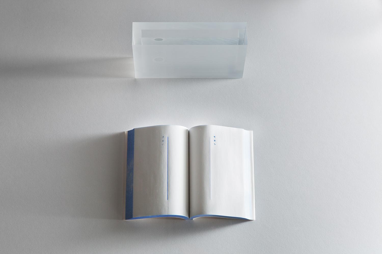 <b>アオイ本 blue book</b>  感圧複写紙、青いインク、アクリル樹脂 carbon paper, blue ink, acrylic acid resin 2014<br><font size=1.5>「伝票などに使われている複写紙。その端から滲むような青い色は、掠れたように奇妙にぼやけ、美しい。<br>ノーカーボン紙、感圧紙といい「筆圧を感知し、文字などを複数枚に渡り写すことが出来る」という。「感圧紙」という聞き慣れない言葉。<br>その紙が「感知し複写する」という。ページを捲るたび、あの薄い紙は応え、アオイ色をみせてくれるのだろうか。」
