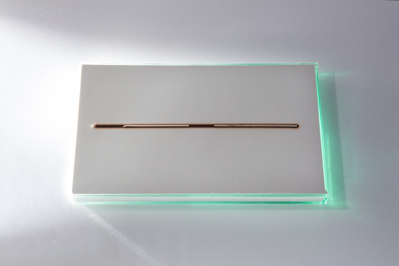 <b>ハイ ヲ ミル watching ash</b> 灰、ガラス ash, glass 2011-14<br><font size=1.5>「線香に火をつけ、白い灰の上に置く。細い枝に似たそれは、緩やかな速度で灰色にかわるとともに、黒い影を落とす。<br>カタチが「カゲ」にかわるとき、突然線香花火に似た赤い光は現れ、消えた。どれほどの時間だったのだろうか。優しい映像。灰のうえの美しい「絵」。」