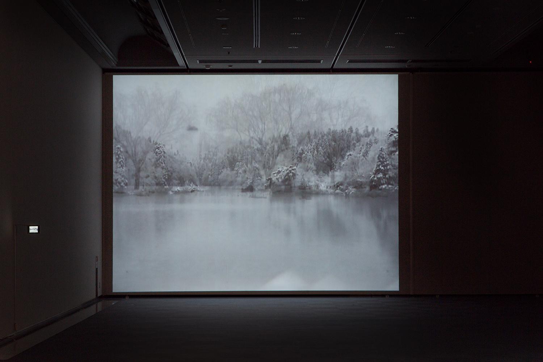 <b>ユキ - 2012|snow -2012</b> プロジェクター、小型液晶ディスプレイ、メディアプレイヤー|projector, LCD TV, media player 2012-14<br><font size=1.5>「四年前より、十二月にはいり、雪が降りだせば、車を走らせ家をでる。琵琶湖沿いに北へ向かい、余呉から日本海まで行くこともあれば、高島の山の方へ入ることもある。<br> 地図も見ず、ただ雪を追っていくだけだ。気が向けば一泊することもあるが、殆どは陽が沈むと家へ帰る、そんな少し遠出の散歩。<br>また、もちろん一冬に二、三度、我家でもカナリの雪が降ることがあり、その時は、長靴を履き、ポットに珈琲を入れ、近所を歩く。夜中の散歩である。」
