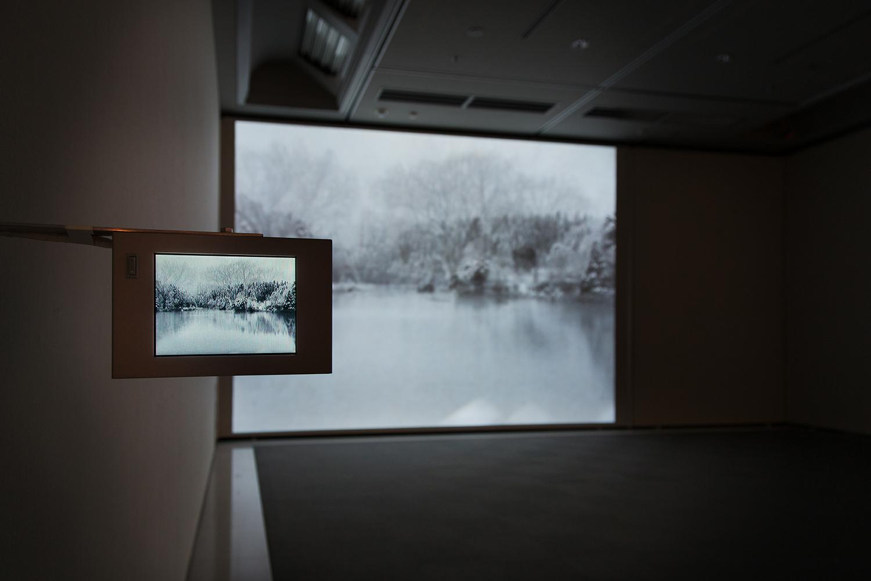 <b>ユキ - 2012|snow -2012</b> プロジェクター、小型液晶ディスプレイ、メディアプレイヤー|projector, LCD TV, media player 2012-14<br><font size=1.5>「ここと思えば、三脚を立てカメラを三分ほど開く、それを何度も繰り返す。六十二分のテープが終わる頃、身体は芯から冷え、帰りたくなる。<br>今年で五度目の冬の散歩。私は妙に気に入っている。家に帰り、マックのうえで「雪の風景」を重ねる。幾重にも重ねた「風景」は、まるで眠りの中のようだ。<br>時間軸の中でみているのではなく、ただ降る「雪」があるだけだ。」