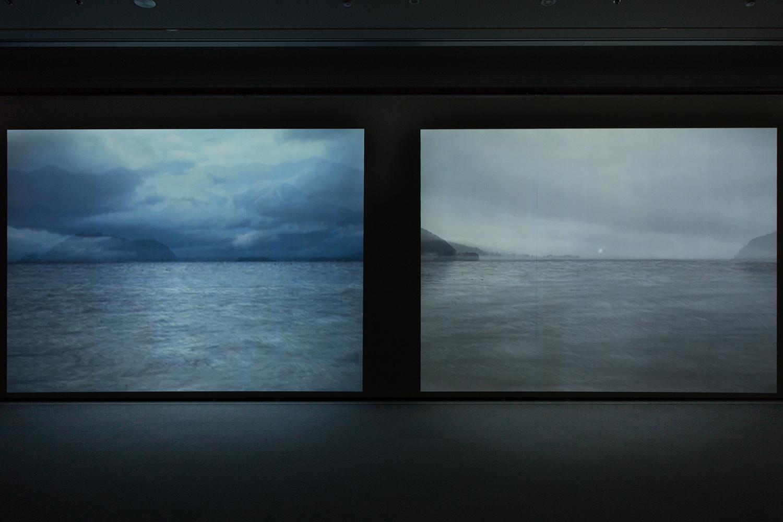 <b>夕日/遠景の座標(左)|setting sun/coordinate of distance view :left 波/遠景の座標(右)|wave/coordinate of distance view :right</b><br><font size=1.5>「琵琶湖を廻り、異なる場所、異なる日にカメラをまわした。家に帰り撮った画像をマックの上に重ねる。 水面だけを合わせた風景の[映像]は水だけが揺らいだ。仮に夢の中でみる夢を[映像]と言うならば、その[映像]は動いているのだろうか。<br>最近妙に気にかかる。例えば琵琶湖に立つ。水面が波打つ―[ものごと]が流れる、そんな時間軸で観ているだろうか。ただ波打つ「水面」を観ているだけだと思えてしかたない。<br>上手くは言えないが、其処に時間が存在することはなく、ウゴク「もの」だけがある。[もの]ではない[映像]を手法としてつくりたいと思いだしたのは、いつ頃からだったのだろう。<br> 知人に教えてもらい小さなビデオカメラだけは購入したものの、学校をでて[もの]を触り制作しつづけてきた自分には、なかなか思いきりがつかないままだった。<br> そんな私が、一昨秋、日頃から交流のある四人で「八つの課題」というグループ展をした折「映像作品をつくる」と課題をだし、はじめて[映像作品]をつくった。<br> 自分が想う[映像]を並べ、瞼を閉じることなく[夢]の中を覗いてみたいと願う。「2009 遠景の座標」ノートより」