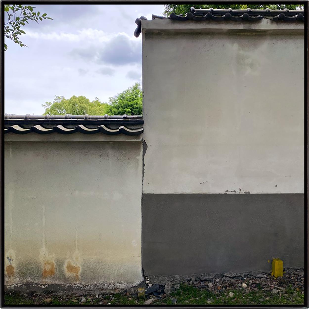 壁を眺める/Looking at a wall|Lambda silversalt print, acrylic board, iron|515 x 515 x 25 mm|2020<br><br>人は二つの目で対象をとらえるが、カメラの場合は一つの「点」から覗く世界を記録する。<br>ある意図をもって空間の中の座標を探し求めシャッターを押すと、無秩序な世界に秩序めいた関係が写る。<br>いつもそんな風景を探している。 正方形という形は四辺が同じ長さの直線で構成されていて、その水平・垂直軸が傾くと重力に逆らう感覚を覚える。<br>カメラは様々なものを写しながら実は重力を写し撮っているのかもしれない。