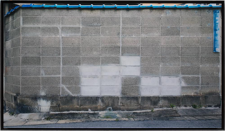 隙間の風景・A/Scenery of the gap|Lambda silversalt print, acrylic board, iron|495 x 855 x 30 mm|2017<br>カメラにはファインダーというのぞき穴があって、そこでとらえた対象を切り取る。ファインダーは四角い形をしていて、カメラによってその比率が違ったり選択が出来たりもする。<br>かつてファインダー比率によって対象との関わり方が違って来ることに気づいてから、トリミングなしで写真を撮ることにしている。これらの写真も矩形の隅々まで神経を使って撮った。<br>ブロックの白い補修跡が2個・4個・6個という倍数になっていてその位置関係も美しい風景だ。
